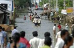 Villagers walk through a flooded road at Ibrahimpatnam in Krishna district of Andhra Pradesh India. Mahesh Kumar Associated Press