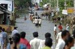 Villagers walk through a flooded road at Ibrahimpatnam in Krishna district of Andhra Pradesh India. Mahesh Kumar Associated Press